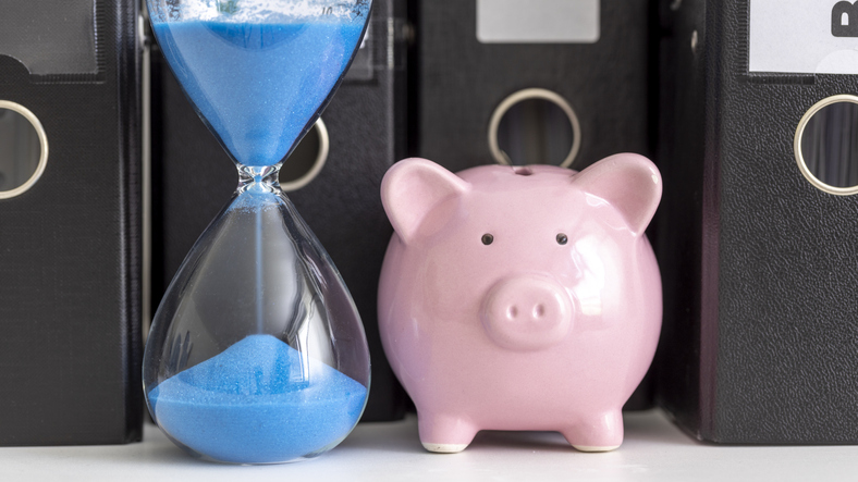 Pink Piggy Bank and hourglass in front of black folder